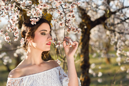 the tree to blossom: Portrait of young woman in the flowered garden in the spring time. Almond flowers blossoms. Girl dressed in white like a bride.