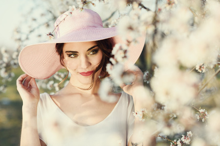 Portrait of young woman in the flowered field in the spring time. Almond flowers blossoms. Girl wearing white dress and pink sun hat