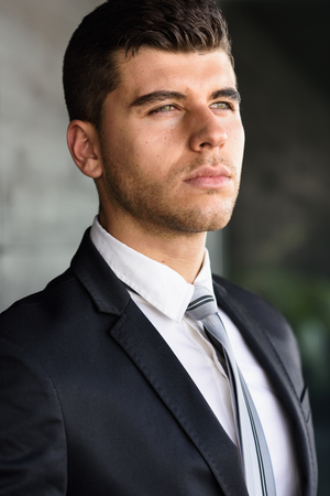 blue eyes: Young businessman near a modern office building wearing black suit and tie. Man with blue eyes 스톡 사진