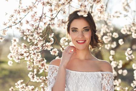 봄 시간에 꽃된 정원에서 웃 고 젊은 여자의 초상화. 아몬드 꽃이 피고. 소녀처럼 신부 흰색 옷.
