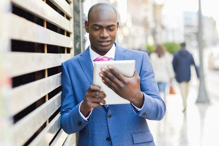 traje formal: Retrato de un hombre de negocios llevaba traje negro mirando a su computadora de la tableta en el fondo urbano
