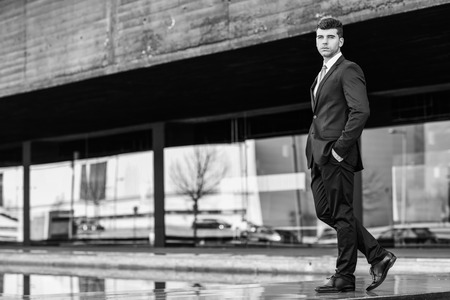 good looking man: Young businessman near a modern office building wearing black suit and tie. Man with blue eyes Stock Photo