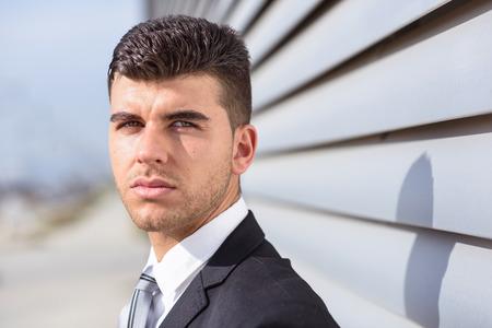 ojos azules: Hombre de negocios joven cerca de un edificio de oficinas moderno vistiendo traje negro y corbata. Hombre con los ojos azules