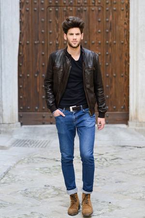 shirt: Portrait of a young handsome man, model of fashion, with modern hairstyle in urban background