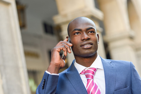 black male: Portrait of a black businessman wearing suit talking with his smartphone in urban background