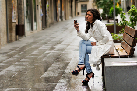 rain: Portrait of beautiful young woman in urban background talking on phone Stock Photo
