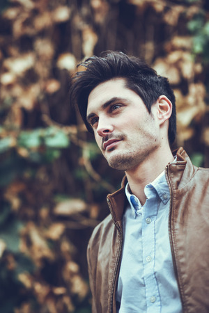 model male: Portrait of a young handsome man, model of fashion, with modern hairstyle in urban background, wearing casual clothes.