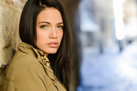 PRETTY WOMEN: Portrait of brunette young woman with green eyes, wearing a coat, in urban background