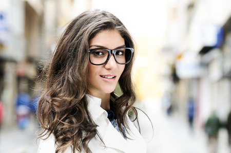 Portrait of a beautiful woman with eye glasses smiling in urban background