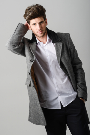 male hair: Portrait of handsome man, model of fashion, wearing coat. Studio shot