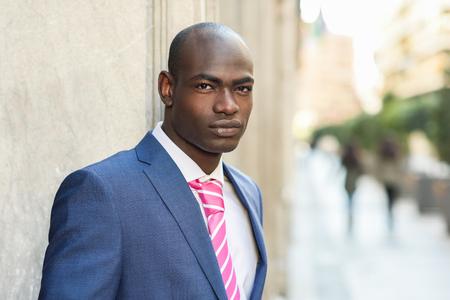 Portret van knappe zwarte man gekleed pak in stedelijke achtergrond