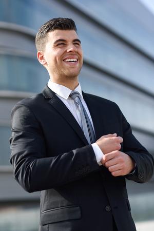 traje formal: Hombre de negocios joven cerca de un edificio de oficinas moderno vistiendo traje negro y corbata. Hombre con los ojos azules sonriendo.
