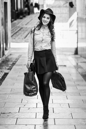 Beautiful brunette young woman wearing short skirt and denim shirt walking on the street with shopping bags