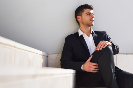 men in suit: Young businessman near a modern office building wearing black suit and white shirt sitting on the floor. Man with blue eyes in urban background
