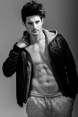 sexy abs: Portrait of athletic man wearing hoodie jacket. Studio shot