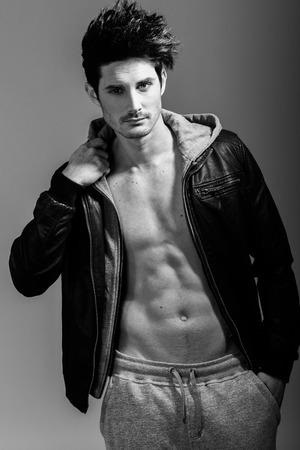 modelos hombres: Retrato de hombre atlético vistiendo chaqueta de la sudadera con capucha. Tiro del estudio