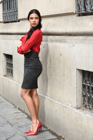 formal shirt: Portrait of hispanic bussinesswoman in urban background wearing red shirt and skirt