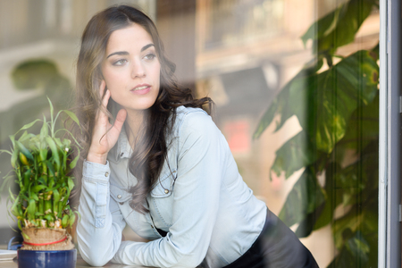 long hair brunette: Cafe city lifestyle. Young woman sitting indoor in trendy urban cafe looking through the window. Cool young modern caucasian female model in her 20s