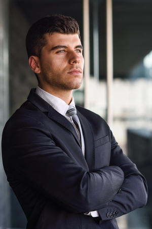 hair tie: Young businessman near a modern office building wearing black suit and tie. Man with blue eyes Stock Photo