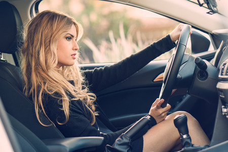 Blondie young girl driving a sport car looking at the road
