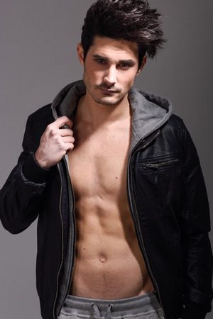 muscular body: Portrait of athletic man wearing hoodie jacket. Studio shot