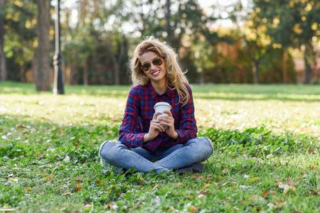 Jonge gelukkige vrouw in geruit hemd en blauwe spijkerbroek met toothy Glimlach en zonnebril. Blondemeisje het drinken koffie in parkzitting op gras die vrijetijdskleding het glimlachen dragen