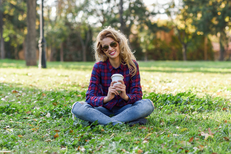 Young happy Woman in checkered shirt and blue jeans with toothy Smile and sunglasses. Blonde girl drinking coffee in park sitting on grass wearing casual clothes smiling Stock Photo