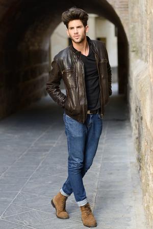 in jeans: Retrato de un hombre hermoso joven, modelo de moda, con el peinado moderno en el fondo urbano