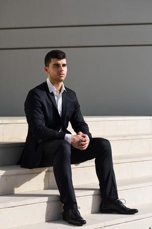 traje formal: Hombre de negocios joven cerca de un edificio de oficinas moderno vistiendo traje negro y camisa blanca, sentado en el suelo. Hombre con los ojos azules en fondo urbano