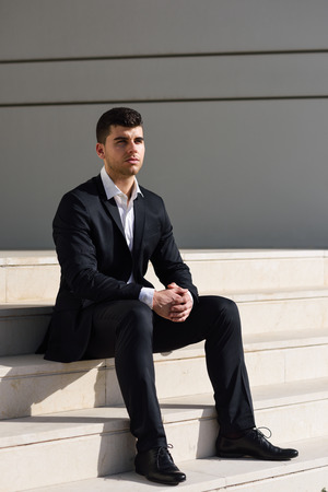 suit: Young businessman near a modern office building wearing black suit and white shirt sitting on the floor. Man with blue eyes in urban background