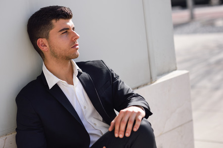 hair tie: Young businessman near a modern office building wearing black suit and white shirt sitting on the floor. Man with blue eyes in urban background