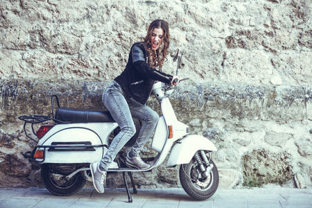 young  brunette: Woman launching a old scooter with pedal wearing casual clothes in urban background.