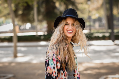 blonde curly hair: Portrait of beautiful young woman looking at camera playing with her curly hair and smiling. Girl wearing jacket and hat.