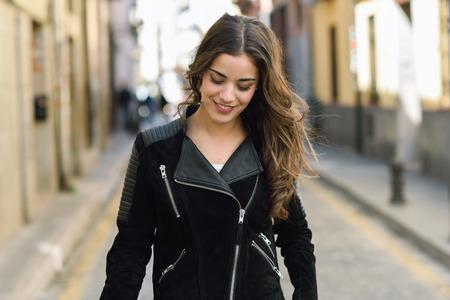 capelli lunghi: Ritratto di giovane donna sorridente in fondo urbano indossando abiti casual con lunghi capelli ricci