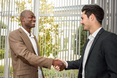 black hands: Black businessman shaking hands with a caucasian one wearing suit in a office. Two men smiling