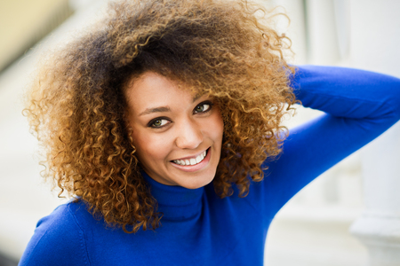 Close-up portrait of beautiful young African American woman, model of fashion, smiling with afro hairstyle and green eyes wearing blue sweater in urban background