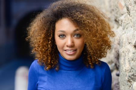 afro 헤어 스타일와 파란 스웨터를 입고 녹색 눈을 가진 아름 다운 젊은 아프리카 계 미국인 여자의 클로즈 업 초상화. 웃는 소녀. 스톡 콘텐츠