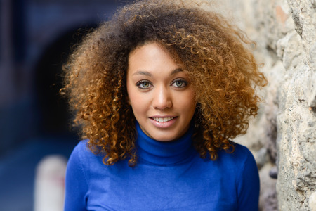 Close-up portrait of beautiful young African American woman with afro hairstyle and green eyes wearing blue sweater. Girl smiling. Фото со стока