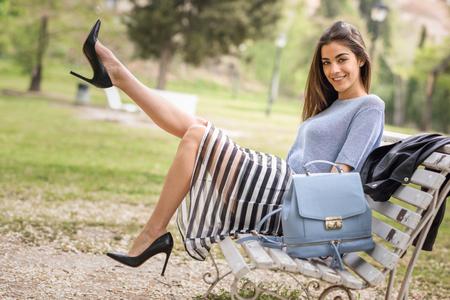 skirts: Retrato de mujer joven con las piernas hermosas en parque urbano con ropa casual. Muchacha que desgasta la falda de rayas, suéter y zapatos de tacón alto