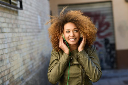 laughing girl: Portrait of young attractive black girl in urban background hearing music with headphones
