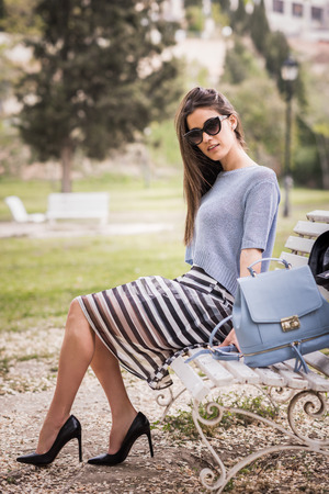 Portrait of young woman with beautiful legs in urban park wearing casual clothes. Girl wearing striped skirt, sweater, sunglasses and high heels