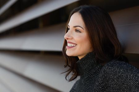 Jonge vrouw die vrijetijdskleding lachend in stedelijke achtergrond. Meisje met mooie glimlach