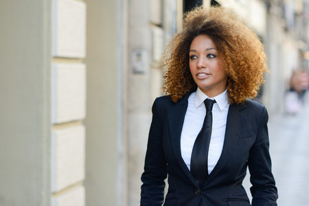 african fashion: Portrait of beautiful black businesswoman wearing suit and tie in urban background