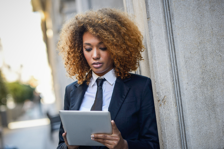 Beautiful black curly hair african woman using tablet computer in town. Businesswoman wearing suit with trousers and tie