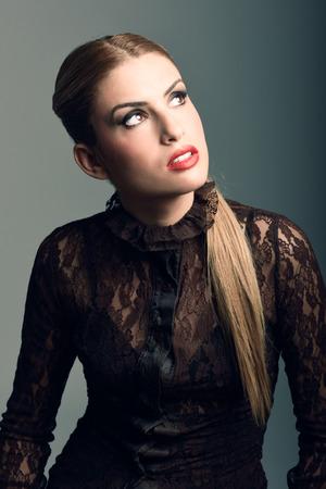 mujeres fashion: Mujer rubia que usa la camisa con una cola de caballo. tiro del estudio