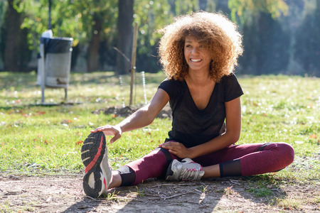 woman stretching: young fitness black woman runner stretching legs after run