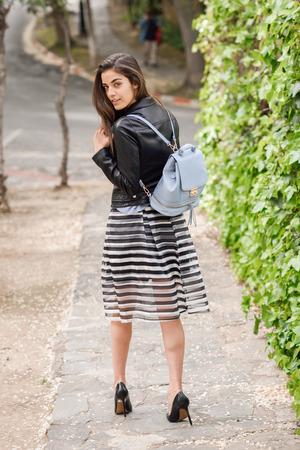 falda: Volver retrato de mujer joven en fondo urbano con ropa casual. Chica con falda a rayas y chaqueta de cuero
