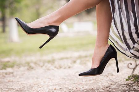 Czarne buty na obcasie na nogi młodej kobiety w parku