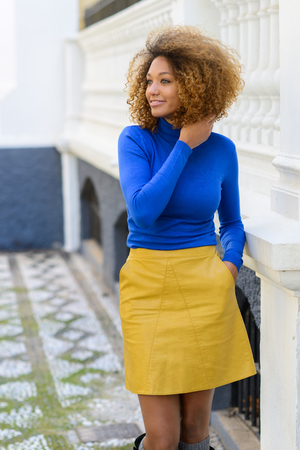 african fashion: Funny young African American woman, model of fashion, smiling with afro hairstyle and green eyes wearing blue sweater and yellow skirt in urban background