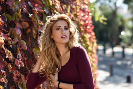 cabello rizado: Mujer hermosa con el pelo rizado rubio en fondo urbano